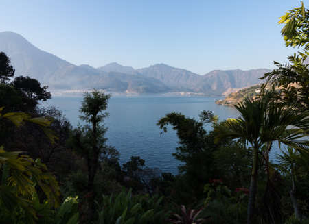 crater highlands: Sunrise at Lake Atitlan in Guatemala formed from volcano crater. Town of San Pedro La Laguna in distance Stock Photo