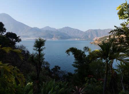 Sunrise at Lake Atitlan in Guatemala formed from volcano crater. Town of San Pedro La Laguna in distance Stockfoto