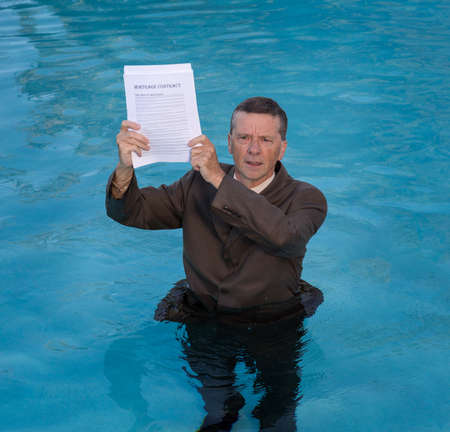 Senior caucasian businessman in suit up to waist in deep blue water worried about being underwater with mortgage payments Stok Fotoğraf