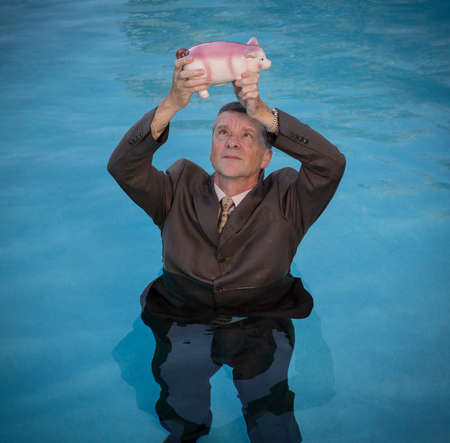 drowns: Senior caucasian man holding piggy bank above water as he slowly drowns in debt wearing business suit