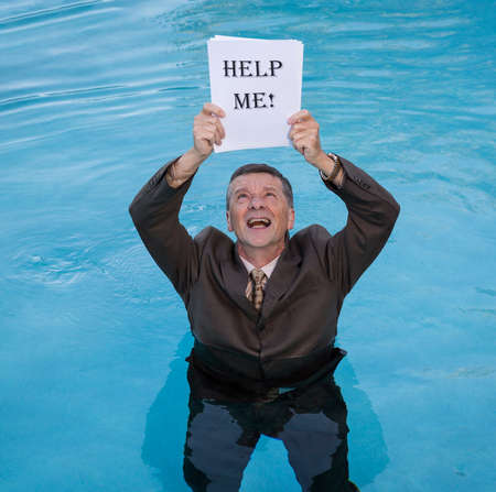 senior depression: Senior caucasian businessman in suit up to waist in deep blue water worried about drowning in paperwork and holding help me document