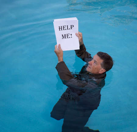 help me: Senior caucasian businessman in suit up to neck in deep blue water worried about drowning in paperwork and holding help me document