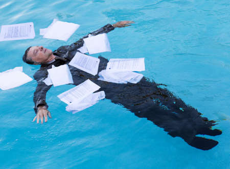 Senior caucasian businessman in suit sinking underwater in deep blue pool worried about being underwater with mortgage payments Stockfoto