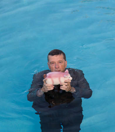senior depression: Senior caucasian man holding piggy bank above water as he slowly drowns in debt wearing business suit