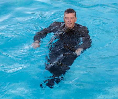 �ber Wasser: Senior kaukasischen Gesch�ftsmann in Anzug bis zur Taille im tiefen blauen Wasser und sah besorgt aus, als er �ber Wasser zu halten versucht Lizenzfreie Bilder