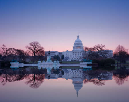 legislature: Brightly lit dawn sky behind the illuminated dome of the Capitol in Washington DC with the pool and statues Stock Photo