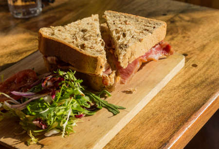 wholemeal: Bacon sandwich on thick wholemeal granary bread on wooden platter on pub lunch table Stock Photo