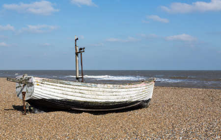 Ancient wooden painted fishing boat on pebble beach by North Sea in Aldeburgh Suffolk on East coast of England Stock Photo