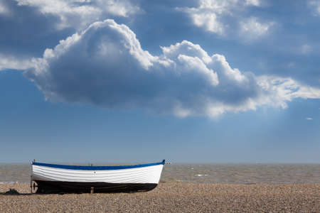 east coast: Ancient wooden painted fishing boat on pebble beach by North Sea in Aldeburgh Suffolk on East coast of England Stock Photo