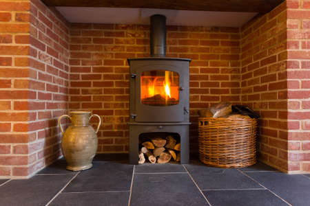 wood cut: Roaring fire inside wood burning stove in brick fireplace with basket of cut wood ready for burning Editorial