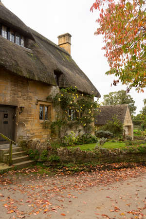 Thatched cottage in Stanton in Cotswold or Cotswolds district of southern England in the autumn. photo