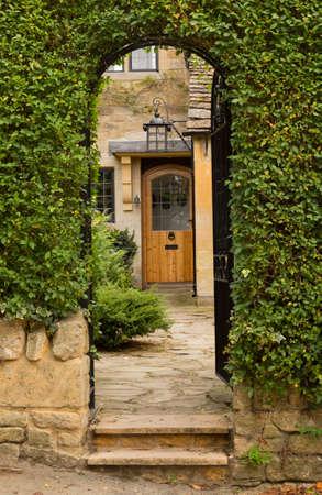 秋に南イギリスのコッツウォルズやコッツウォルズ地区スタントンのコテージの正面玄関への入り口。