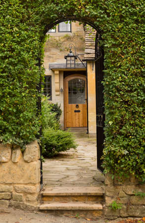 Entrance to front door of cottage in Stanton in Cotswold or Cotswolds district of southern England in the autumn.