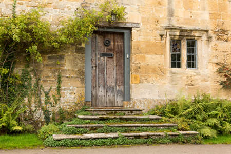 Ancient oak front door to cottage in Stanton in Cotswold or Cotswolds district of southern England in the autumn. photo