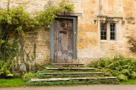 Oude eiken voordeur naar huisje in Stanton in Cotswold of Cotswolds district in het zuiden van Engeland in de herfst.