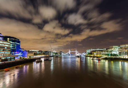 Floodlit HMS Belfast, Tower Bridge and Tower of London on River Thames with reflections in the water photo