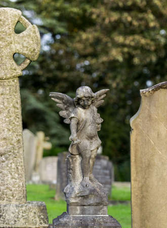 angel cemetery: Statue of angel above grave of dead girl in old cemetery in Shropshire in England