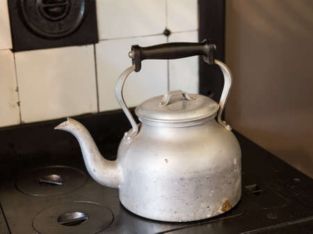 Old fashioned metal kettle sitting on cast iron black cooker hob with tiled surround photo