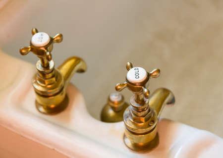 真鍮や銅にホットとコールドに刻まれたトップでアンティークの古いお風呂をタップします。