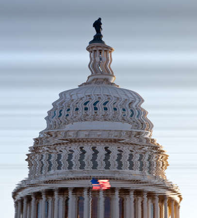 US flag flies in front of the US Capitol in Washington DC in submerged distorted view of the dome of Congress building