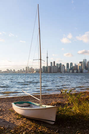 beached: Single sailing boat beached on sandy shore of Lake Ontario on Wade Island of Toronto Islands with skyline