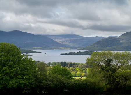 eire: Sun breaks through the clouds to light the meadow and Killarny Lake in Kerry Ireland or Eire