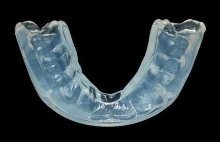 マクロは黒に対して隔離される夜の研削歯により、摩耗を停止するプラスチック歯ガードのクローズ アップ。多くの場合緊張と心配によって引き起こされます。 写真素材 - 23326216