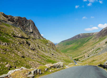 cumbria: Narrow road leads down from Honister Pass in the English Lakes or Lakeland Lake District in Cumbria