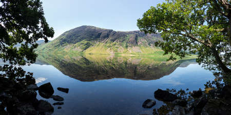 cumbria: Mirror like reflection of the Lake District hills surrounding Crummock Water framed by the trees on the lakeside. Idyllic image from the English Lakes