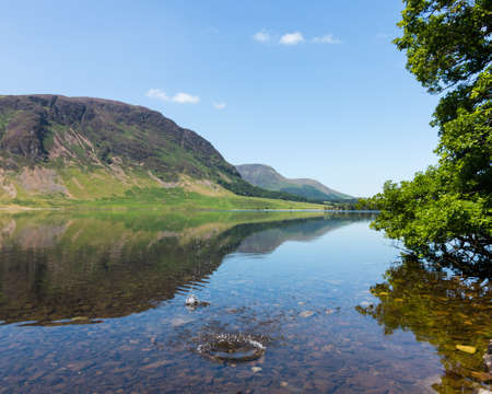 Mirror like reflection of the Lake District hills surrounding Crummock Water with a splash from thrown stone spoiling the smooth surface. Idyllic image from the English Lakes
