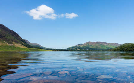 cumbria: Mirror like reflection of the Lake District hills surrounding Crummock with a very low viewpoint emphasizing the water. Idyllic image from the English Lakes Stock Photo