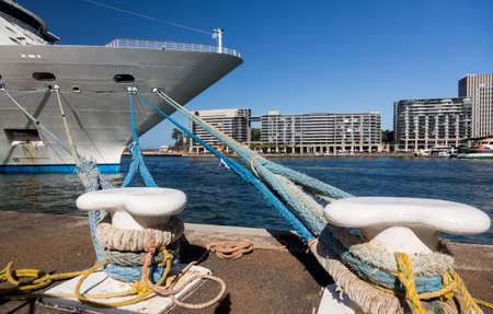 mooring bollards: Dramatic image of the city of Sydney with the bow of a cruise ship docked in the harbor with the focus on the bollards and ropes mooring the boat to the harbour wall