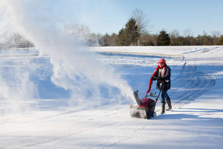 Senior lady using a snowblower on rural drive on windy day with a cloud or blizzard of snow blowing in the air photo