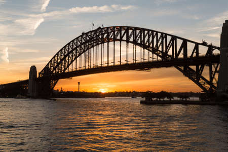 glowing ball: Sun sets in orange glowing ball under the silhouette of Sydney Harbour Bridge in Australia Stock Photo
