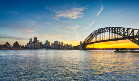 Dramatic widescreen panoramic image of the city of Sydney at sunset including the Rocks, Bridge, Opera House, and a broad view of CBD and the water in the harbour