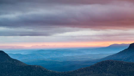 lookout: Rising sun illuminates clouds and mist in the valley from Echo Point overlooking the majestic Blue Mountains near Sydney NSW Australia