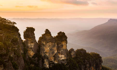 rock formation: Rising sun illuminates the Three Sisters rock formation in the valley from Echo Point overlooking the majestic Blue Mountains near Sydney NSW Australia Stock Photo