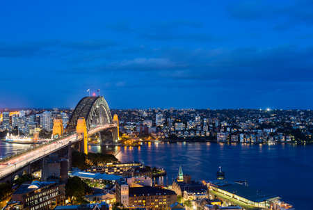 sydney harbour: Dramatic widescreen panoramic image of the city of Sydney at night including the Rocks, Bridge and Luna Park and a broad view of the water in the harbour Stock Photo