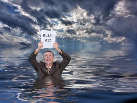 Conceptual image of senior businessman in suit up to waist in deep water worried about drowning in paperwork and holding help me document. Stormy clouds behind reflect in the ocean. photo