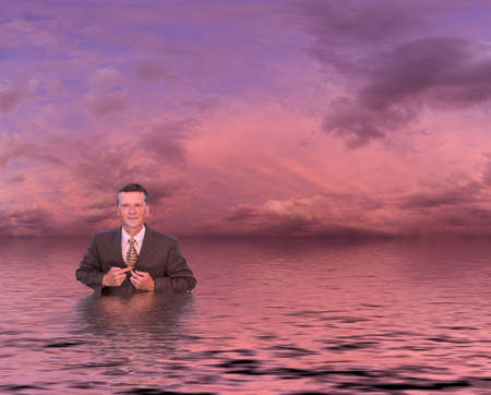 Conceptual image of senior businessman in suit up to waist in deep water. Man is looking proud and confident and the sunset reflects an image of success and not drowning in problems photo