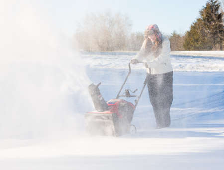 Young lady using a snowblower on rural drive on windy day with a cloud or blizzard of snow blowing in the air and covering her with icy snow photo
