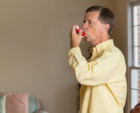 asthmatic: Senior caucasian man at home with asthma inhaler to handle problems with breathing Stock Photo