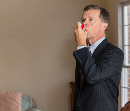 bronchial: Senior caucasian man  in suit at home with asthma inhaler to handle problems with breathing