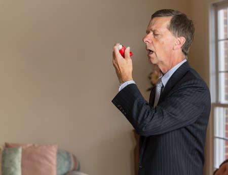 asma: Hombre caucásico mayor en juego en casa con inhalador para el asma para manejar problemas con la respiración Foto de archivo