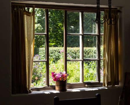 Uitzicht op cottage tuin achter een traditioneel Engels tuin in de zomer met kleine bakstenen huisje huis en bloeiende planten en bloemen Stockfoto
