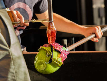 Glass blower artists work on adding decoration to ornate green glass bottle or bowl photo