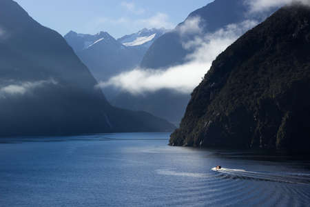 Sailing into Milford Sound on South Island of New Zealand in early morning as the sun rises above the mountains photo