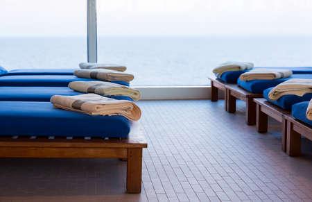 Rij van teak liggende banken of banken met kussens en een handdoek door raam met uitzicht op de zee met de horizon in de verte