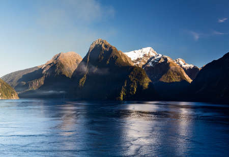 fiordland: Sailing into Milford Sound on South Island of New Zealand in early morning as the sun rises above the mountains Stock Photo