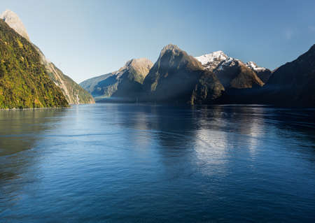 Sailing into Milford Sound on South Island of New Zealand in early morning as the sun rises above the mountains Stock Photo